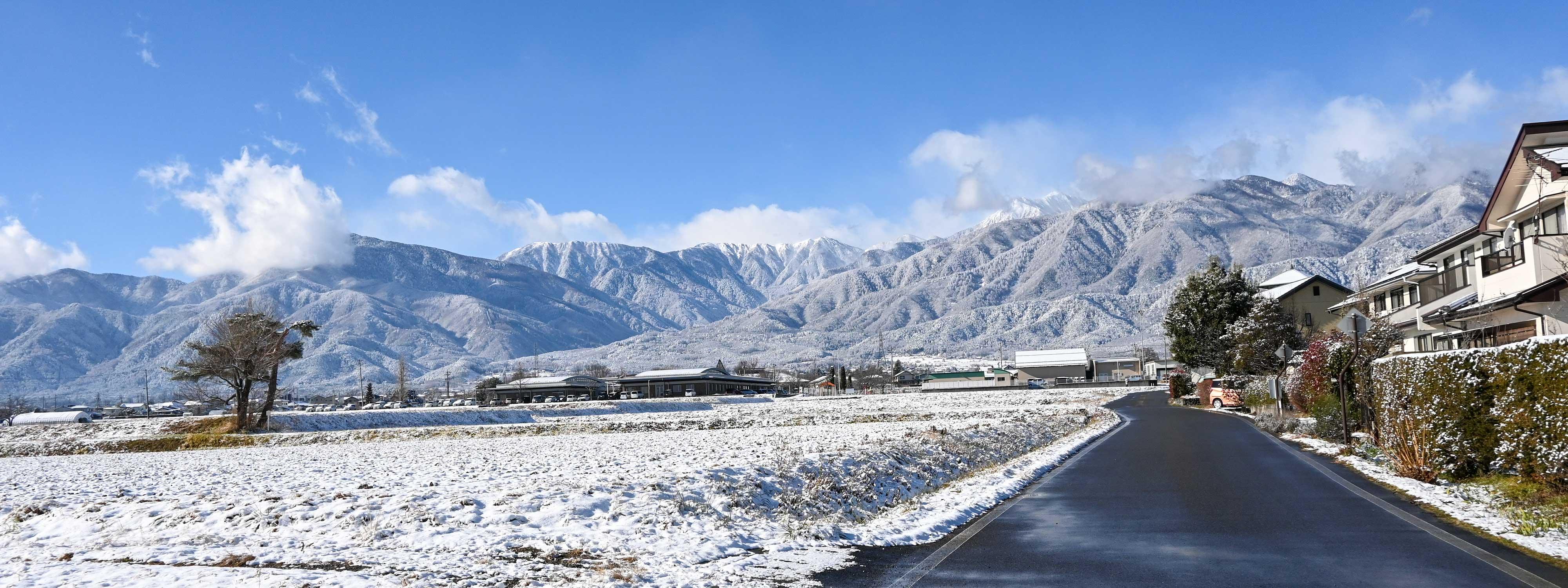 2020/12/17【雪あがりの安曇野の朝】穂高駅から10分ほど歩くと、街並みの向こうには常念岳、蝶ヶ岳が雲間から見えてきました。